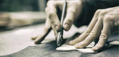 Bespoke shoes being made, photo shows leather being cut by hand
