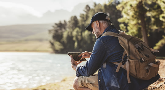 Photo of man using a tablet while hiking by a loch